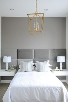 White and gray bedroom features a full length gray padded headboard mounted on wall lined with a bed dressed in white bedding as well as gray and silver striped pillows flanked by white floating night Gray Upholstered Headboard, Floating Headboard, White Headboard, White Nightstand, White Dressers, Floating Nightstand, Gray Bedroom, White Bedding, Trendy Bedroom