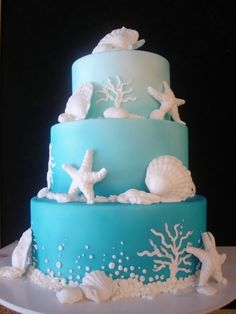 Gorgeous blue ombre cake with white sea-themed decorations