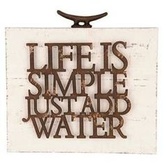 """Everything's easier at the beach! Display this shore-loving statement for all to see with our """"Life Is Simple Add Water"""" Wall Art. Whitewashed wood is contrasted by the distressed wood lettering and rustic metal hardware. Combine it with our other nautical-themed wall decor for a cohesive look, or display it on its own in a beach cottage or lake house."""