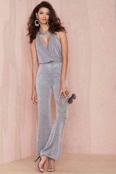 Delirium Metallic Halter Jumpsuit   Halter in the name of love. The Delirium Jumpsuit is made in a silver metallic fabric and features halter design, straight-leg silhouette, crossover bodice, and deep v-neckline. Open back, back zip closure, ties at neck. Partially lined. Wear it with a wide brim hat and peep-toe platforms.