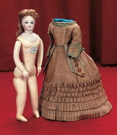 Petite French Bisque Poupee, circa 1870, with original bronze silk gown,undergarments and shoes.