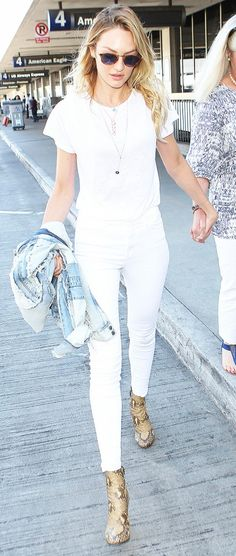 Candice Swanepoel sports an all-white outfit with a pop of snake print booties.
