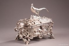A silvered bronze casket signed Auguste Cain A silvered bronze casket signed by Auguste Cain (1821-1894) topped with a pheasant, with two handles and four legs made of tree branches. Of the two main sides, oval niches are decorated on one hand with two rabbits and the other three partridges. The box is richly decorated with branches and mulberry fruit and nut trees. All the decorative elements of this box are in high relief which gives much life to this casket.