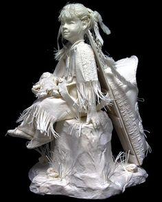 """""""The Babysitter"""" de Allen et Patty Eckman. Cette sculpture de papier raconte l'histoire d'une jeune fille Lakota assise sur un rocher, poupée à la main, son petit frère est endormi dans son porte-bébé."""