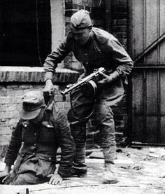 A Soviet soldier drags a captured German out of his underground hiding place at gunpoint during fighting in Berlin, 1945
