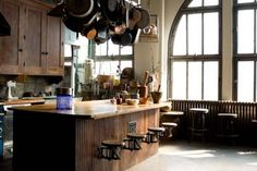 kitchen: Love the open space, seating, wood, and pots and pans hanging above.