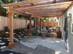 A water efficient back yard with a redwood pergola that has clear corrugated plastic for a roof.