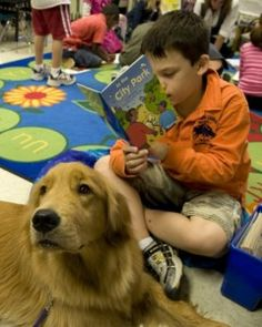 Dogs have long helped out in the classroom, sometimes with reading programs (pictured) and stress relief: Now, canines are being recruited to help teach compassion anD reduce bullying.