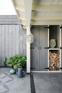 Summer style!! Storage with Style! Elegant pale gray covered terrace, veranda, patio - with the elegant storage for outdoor garden items! This is the way to do outdoor storage!! Also -- notice the long metal drain too -- excellent idea for stormwater and rainwater control!