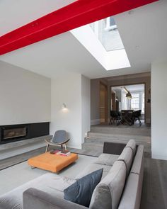 The extension steps down from the dining room, and the ceiling follows suit. The skylight and window wall focus daylight through the back of the original house.