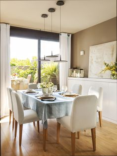 IMG 8722-1. Comedor con sillas tapizadas en blanco con un ventanal a la terraza_IMG 8722-1
