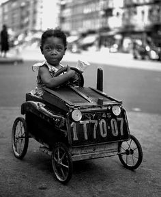 CAUTION! STUDENT DRIVER ON BOARD   1947 – Unidentified African American girl driving a makeshift pedal car. Photo by Fred Stein, Harlem, New York City, 1947. [website]