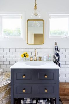 A Restoration Hardware Bristol Flat Mirror is mounted to a white wall between square windows and is illuminated by a glass and brass conical sconce fixed over a dark blue washstand accented with gold knobs and a white quartz countertop holding a sink with a brass gooseneck faucet in front of white subway backsplash tiles.