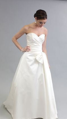 Itallian Silk Duchess strappleess gown finished with a classir Dior Bow and trimed with a French Alencon Trim.