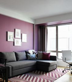 Rich use of color in this Contemporary Living Room. The purple walls and purple rug pop but the simple grey couch mellows the room by Victoria Elizabeth Design.