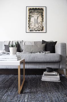 A moody monochrome living room with white walls, grey sofa and dark rug