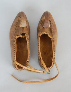 A pair of Serbian man's leather shoes with leather thonging and with a decorative 'horn 'or 'serpent' folded back over a plaited leather front panel. The lower edges are joined by…