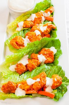 Buffalo Chicken Lettuce Wraps with Blue Cheese Dressing by Plating Pixels. Rich and tangy buffalo chicken sauce with blue cheese dressing in a lettuce wrap make a perfect quick party appetizer. - www.platingpixels.com