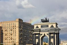 Rainbow over the Triumphal Arch of Moscow on Kutuzovsky Avenue ( Kutuzovsky Prospekt ). Residential house in the Stalinist style in the background. Moscow, Russia.