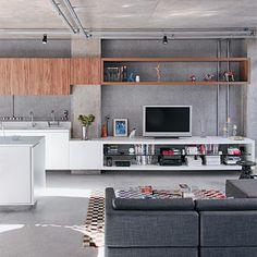 Casa 1. Harmonia em cinza. Revestido de fulgê com grãos brancos, pretos e acinzentados, o paredão repete o tom predominante da construção e valoriza a composição do ambiente.