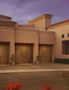 """Depending on the """"species"""" you choose, Clopay's Canyon Ridge Collection faux wood garage doors can have a either a smooth, traditional appearance or take on a rustic, Southwestern flair like on the house shown here. Door Model: Design 12 with solid Top Panel 11. Pecky Cypress cladding with Clear Cypress Overlays."""