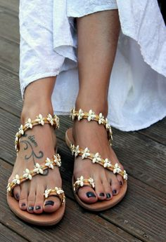 Genuine leather Greek sandals, handmade to order.   A luxury pair of sandals, hand sewn not glued, decorated with a gold plated braid full of gleaming crystals and white opal daisies. So elegant flat shoes for every special occasion where you will be well-dressed without wearing high-heels. A perfect choice for weddings especially boho weddings. They called Santorini of course because of the wonderful cosmopolitan Greek island Santorini.   Sizes available…