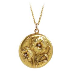 Art Nouveau Diamond Yellow Gold Floral Design Locket. Art Nouveau 10K yellow gold locket with floral 3 dimensional relief design, with two European cut diamonds suspended from an 18k yellow gold, 22 inch cable chain. c 1900