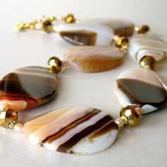 Lovely large agates in peachy pink and brown stripes are dressed up with small pink freshwater pearls, faceted bronze crystal rondelles and tiny gold plated spacers. Each agate stone is a rounded oval twist shape and polished until they gleam. The natural patterns and color variations make these stones stand out on their own, yet blend together perfectly! Beads are strung on gold flexible beading wire and secured with crimps and wireguards. The crimps are hidden with gold plated crimp c...
