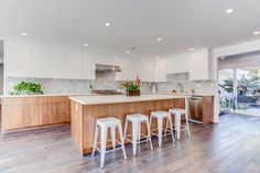 simple white countertop with wooden cabinet below and white high chair for 4