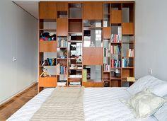 Estante vazada de perobinha, criada pelos arquitetos, separa o quarto do closet, que foi instalado na metade da área do antigo banheiro. Roupa de cama da Trousseau (Foto: Maíra Acayaba)