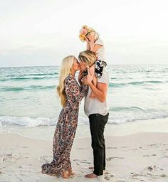 Mom, dad, and child dressed up on the beach