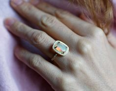 Beautiful halo engagement ring with colorful cushion cut opal. This ring can be made also with other gemstones per request. This ring is handmade. It