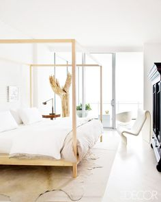 Bedroom with white walls, white bedding, white floors, white chair, beige rugs, wooden bed frame, and wooden bedside table