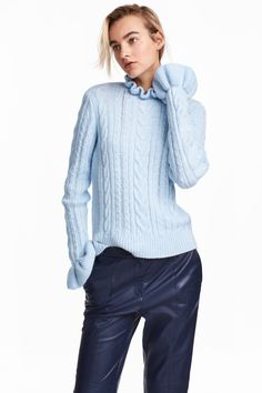 Light blue. Soft cable-knit sweater. Small ruffled collar and long sleeves with ruffled cuffs.