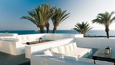 Just love the white outdoor furniture against the blue sky- like a greek island sitting in the blue sea