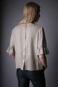 Straight silhouette, with fastening at back with 6 shell buttons and sleeves with double gathering. At front top - yoke and gathering under the yoke. At