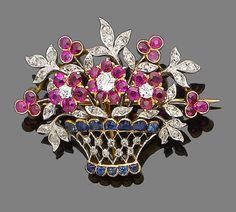 A ruby, sapphire and diamond giardinetto brooch  Designed as a basket of flowers, the flowerheads set with circular-cut rubies and old brilliant-cut diamonds, with rose-cut diamond-set leaves and circular-cut ruby trefoils, the openwork basket set with vari-cut sapphires and rose-cut diamonds, French assay marks, length 3.5cm