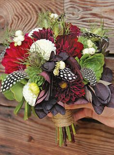 Bouquet of dahlias, snowberries, nigella pods, succulents, and smoke-bush foliage, with guinea hen feathers    by The Cutting Garden at Flora Grubb Gardens, San Francisco