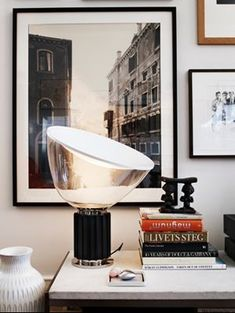 The FLOS Taccia table lamp adds a warm glow to this desk space filled with framed photographs and colorfully stacked books.