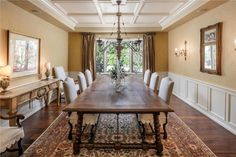 Dining Room: Beautiful formal dining space with a coffered ceiling, stunning chandelier, wainscot paneling and front bowed window.