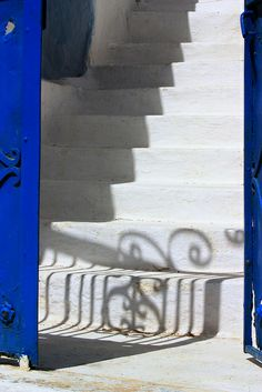 Blue open gate, steps and shadows at Koronos on Naxos Island, Greece