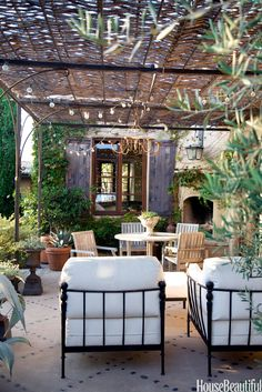 A chandelier and string of lights add even more romance to the patio of a Corona del Mar, California, house designed by owner Dana Abbott and her design partner, Kim Fiscus. A simple grid of black river rocks add an elegant detail in the concrete patio. Amy Neunsinger  - HouseBeautiful.com