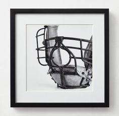 RH TEEN's Vintage Sports Gear Photography - Catchers Mask:High-contrast black-and-white images of vintage sports gear – purposefully cropped to enhance their abstract, orderly appeal. Choose a single likeness or hang in multiples, paying homage to the sporting life.