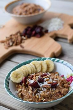 Blue rimmed bowl containing steel cut oats topped with sliced bananas, dried cranberries, coconut flakes and sliced pecans.