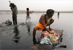Peasants in New Delhi bathe and wash their clothes in the Yamuna River a noxious black stream polluted with raw sewage and methane gas.