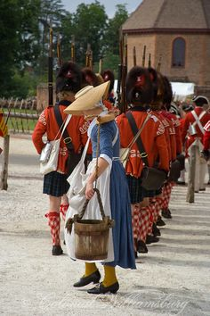"""Woman carrying water at the rear of a column of Redcoats. """"Under the Redcoat"""" re-creation of the British Army's 1781 Occupation of Williamsburg. Colonial Williamsburg's Historic Area, Williamsburg Virginia. Photo by Barbara Temple Lombardi"""