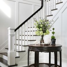 Simple white paneled foyer with antique wooden table. Ready for spring.