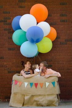 Hot air balloon photo booth at Jack's first birthday. Made it from a crate, batting, and burlap. Tied 36 inch balloons to the top. Pretty proud of how it turned out!
