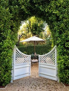 low gate in hedge/pleached hornbeams, to urn with mirror behind and tall gate to left?