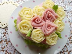 Sushi roses piped mashed potatoes colored and flavored with different herbal vinegars and top off layered sushi rice and veg.